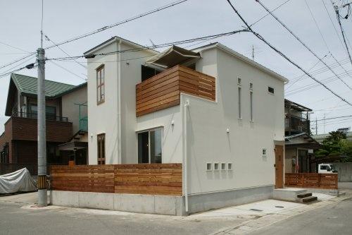 白い塗り壁にレッドシダーの木塀、ポイントになる木窓の外観