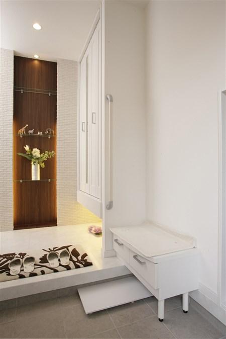 木質の壁紙と間接照明で重厚感を感じさせる玄関